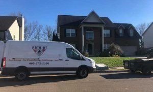 a patriot restoration van in front of a customer's home