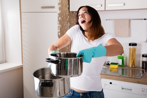 a woman holding pans to catch water from a leaking appliance