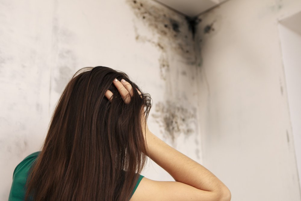 a woman looking worried in front of a wall with mold growing on it